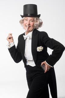 Maureen dressed in a tuxedo and top hat, with a fake cigarette in her mouth